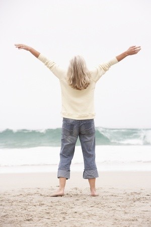 winter escape: Senior Woman With Arms Outstretched On Winter Beach