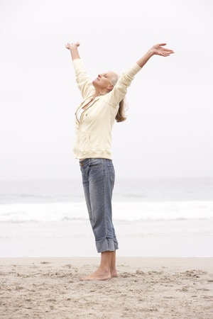 Senior Woman With Arms Outstretched On Winter Beach Stock Photo - 8482976