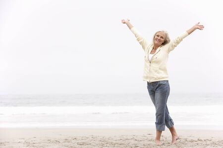 Senior Woman With Arms Outstretched On Winter Beach Stock Photo - 8476406