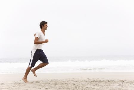 Young Man Running Along Winter Beach photo