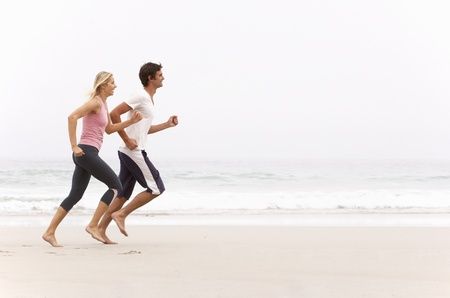 Young Couple Running Along Winter Beach photo
