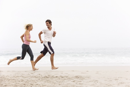 people jogging: Pareja joven correr a lo largo de la playa de invierno