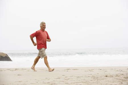 Senior Man On Holiday Running Along Winter Beach Stock Photo - 8476392