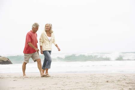 Senior Couple On Holiday Running Along Winter Beach Stock Photo - 8482796