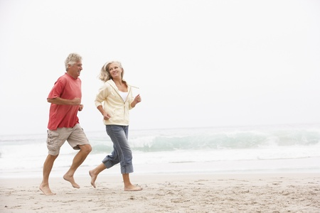 Senior Couple On Holiday Running Along Winter Beach photo
