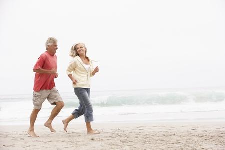 an active: Senior pareja On Holiday correr a lo largo de la playa de invierno Foto de archivo