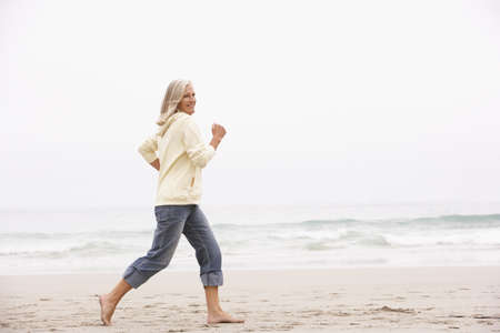 Senior Woman On Holiday Running Along Winter Beach Stock Photo - 8476386