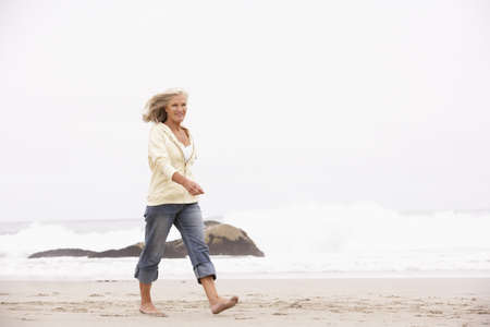 Senior Woman On Holiday Running Along Winter Beach Stock Photo - 8476390