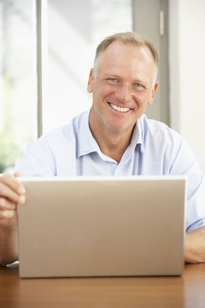 silver surfer: Middle Aged Man Using Laptop At Home Stock Photo