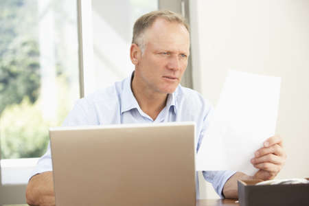 Middle Aged Man Using Laptop At Home photo