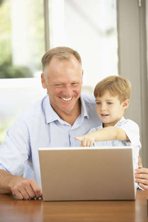 Father And Son Using Laptop At Home photo