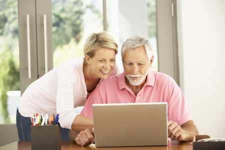 silver surfer: Adult Daughter And Senior Father Using Laptop At Home Stock Photo