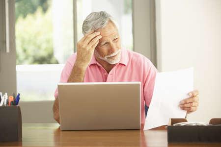 Senior Man Using Laptop At Home photo