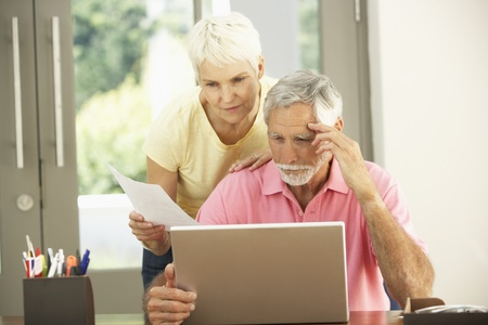 Worried Senior Couple Using Laptop At Home Stock Photo - 8482849