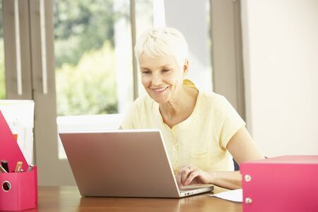 Senior Woman Using Laptop At Home photo