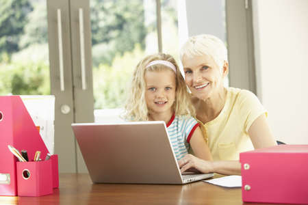 Granddaughter And Grandmother Using Laptop At Home photo