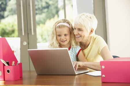 silver surfer: Granddaughter And Grandmother Using Laptop At Home Stock Photo