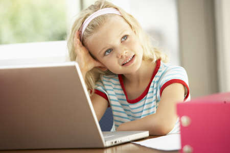 Young Girl Using Laptop At Home photo