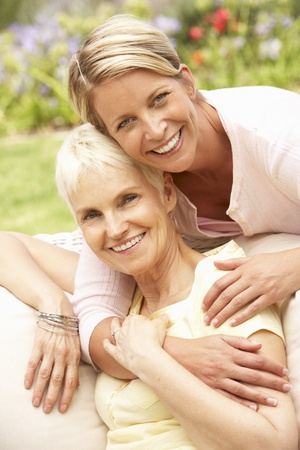 mother on bench: Senior Woman And Adult Daughter Relaxing In Garden