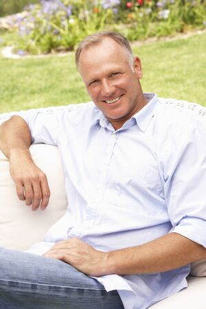 Middle Aged Man Relaxing In Garden Stock Photo - 8483084