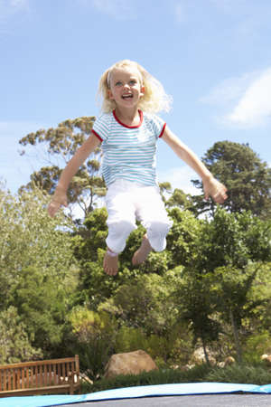 Young Girl Jumping On Trampoline In Garden photo