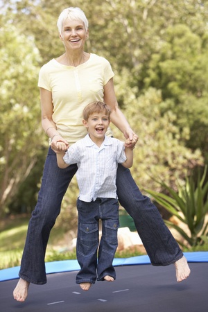 Grandmother And Grandson Jumping On Trampoline In Garden photo