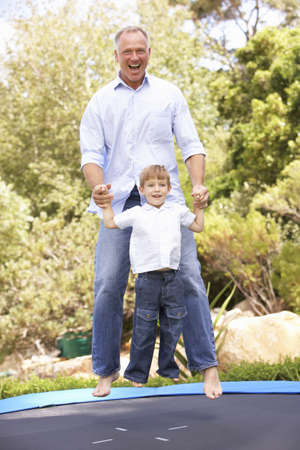 Father And Son Jumping On Trampoline In Garden photo