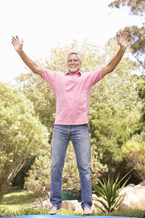Senior Man Jumping On Trampoline In Garden Stock Photo - 8483133