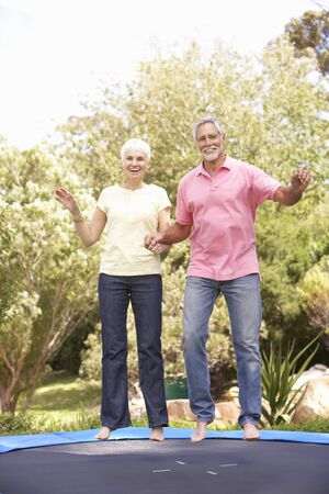Senior Couple Jumping On Trampoline In Garden photo