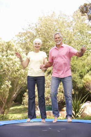 정원에서 트램폴린에 점프 수석 커플