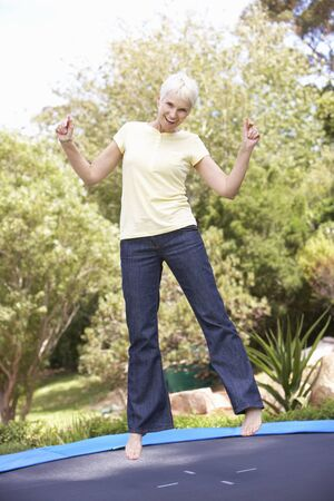 Senior Woman Jumping On Trampoline In Garden Stock Photo - 8483165