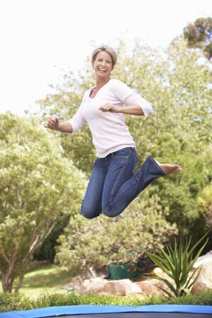 Woman Jumping On Trampoline In Garden photo