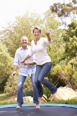 fit couple: Couple Jumping On Trampoline In Garden Stock Photo