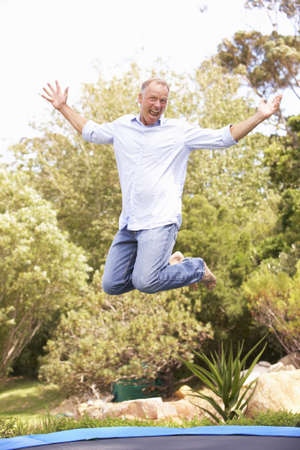 Middle Aged Man Jumping On Trampoline In Garden photo