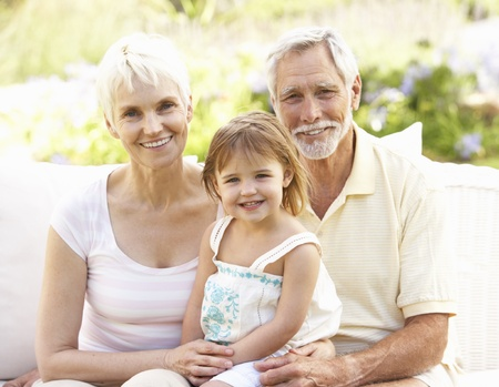 Grandparents And Granddaughter Relaxing In Garden Stock Photo - 8476388