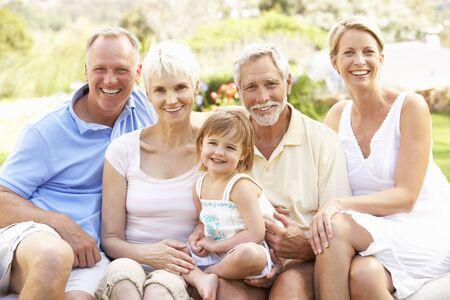familia de cinco: Familia extendida relajante en jard�n Foto de archivo