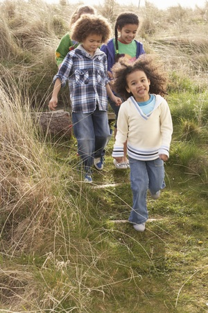 nine year old: Group Of Children Playing In Field Together Stock Photo