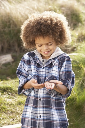 Young Boy Holding Worm Outdoors Stock Photo