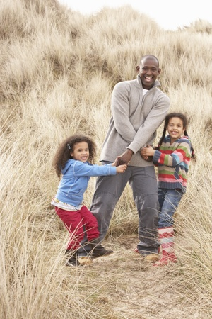 dad and daughter: Father And Daughters Having Fun In Sand Dunes