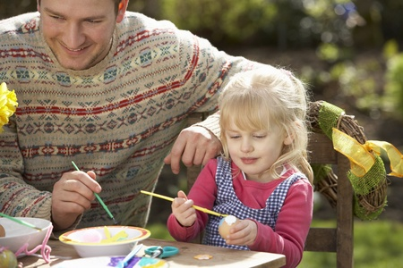 Father And Daughter Decorating Easter Eggs On Table Outdoors Stock Photo