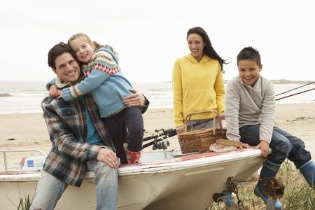 mama e hijo: Grupo Familia que se sienta en el barco con la pesca Rod en la playa del invierno Foto de archivo