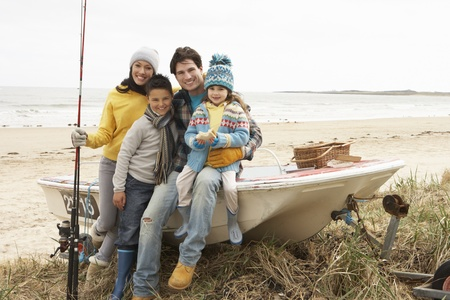 barca da pesca: Family Group Sitting On Boat With Fishing Rod On Winter Beach