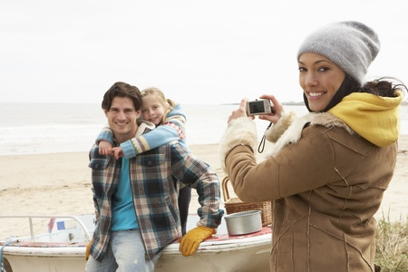 family outside: Mother Taking Family Photograph On Winter Beach