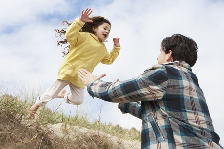 Father And Daughter Having Fun On Beach Together Stock Photo