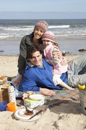 Family Having Barbeque On Winter Beach Stock Photo