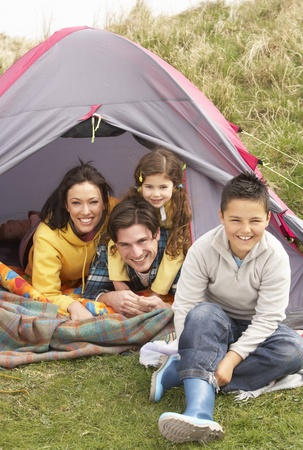 7 year old boys: Young Family Relaxing Inside Tent On Camping Holiday