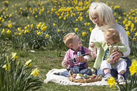 madre hijos: Mother And Children In Daffodil Field With Decorated Easter Eggs Foto de archivo