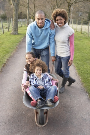 nine year old: Family Having Ride In Wheelbarrow In Countryside