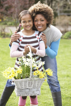 nine year old: Mother And Daughter Holding Basket Of Daffodils In Garden