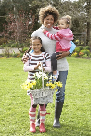 nine year old: Mother And Children Holding Basket Of Daffodils In Garden Stock Photo